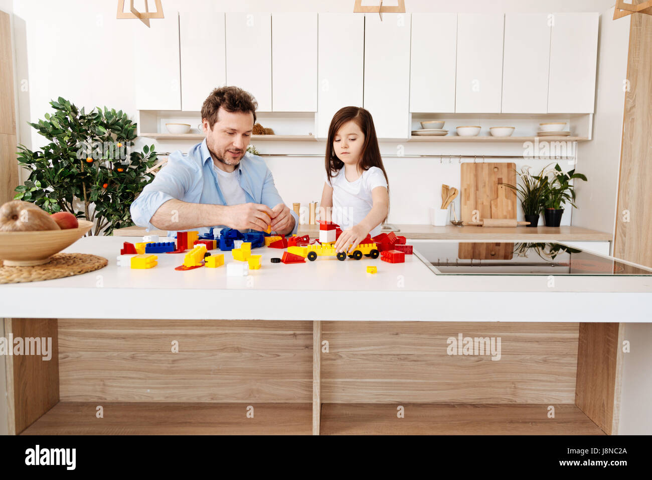 Absolutely concentrated. Young bristled father and daughter sitting in the kitchen at a white counter full of construction - Stock Image