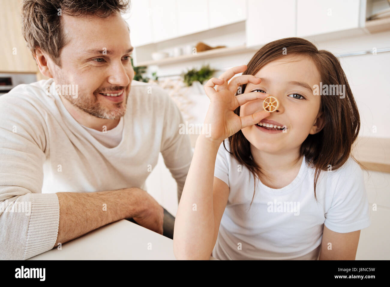 Fooling around. Cheerful cute girl goofing around by pressing a piece of wagon-wheel pasta to her nose while her - Stock Image