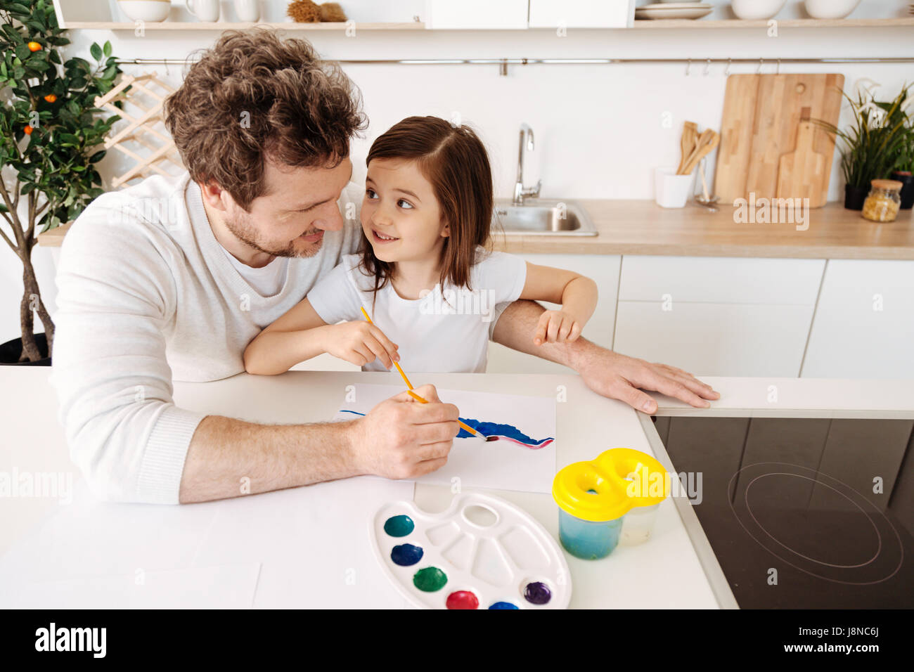 Family co-creation. Merry loving single-parent family bonding to each other while painting together one picture - Stock Image