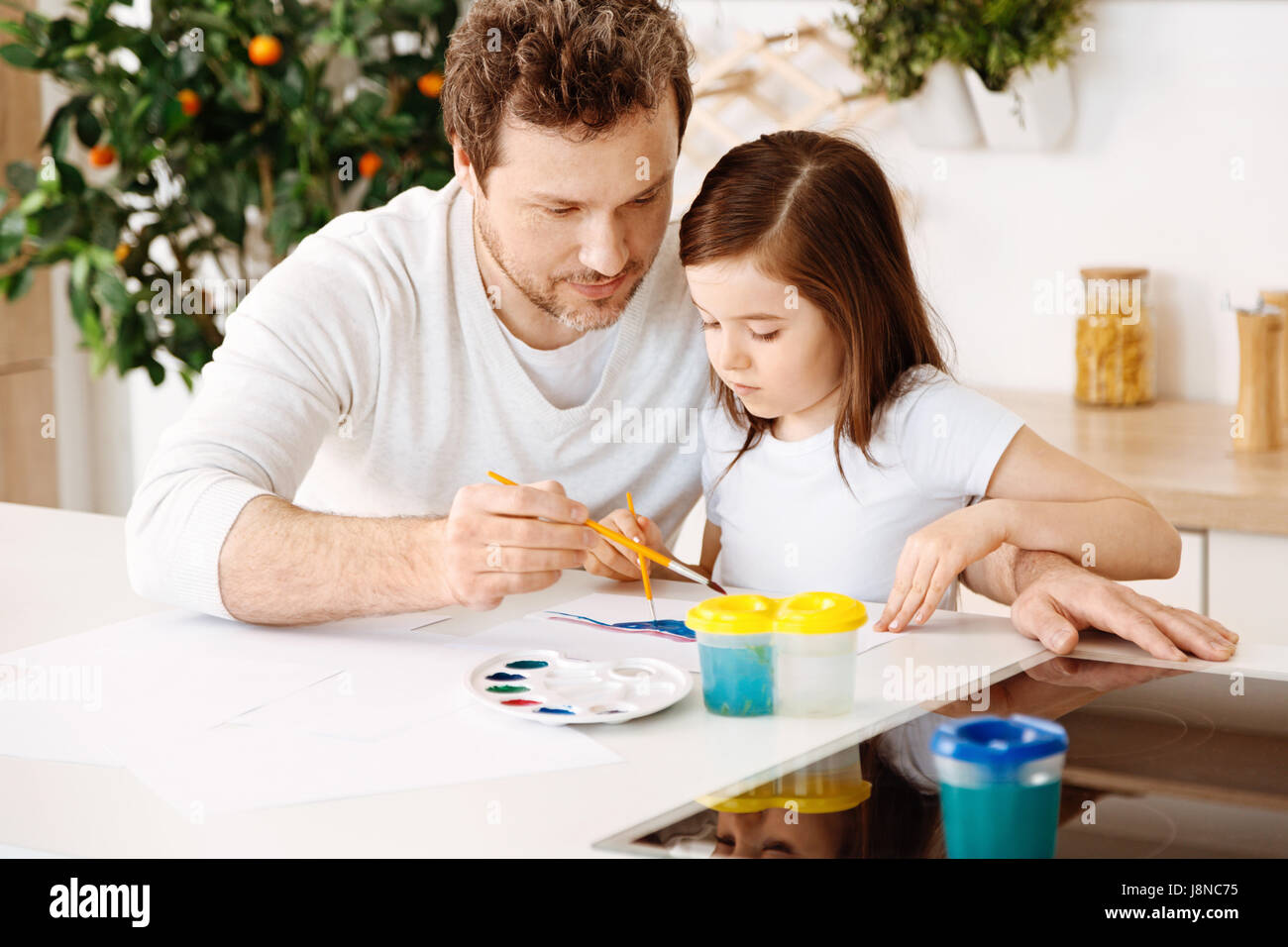 Treasured moments. Inspired loving single-parent family enjoying themselves while painting together one picture - Stock Image