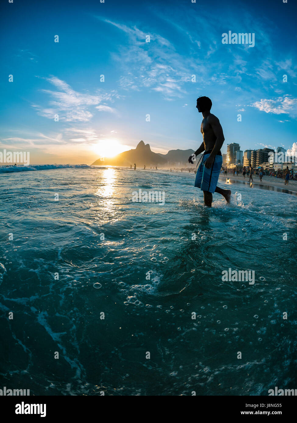 Young Brazilian man walking in silhouette through the waves on Ipanema Beach as the sun sets behind Two Brothers - Stock Image