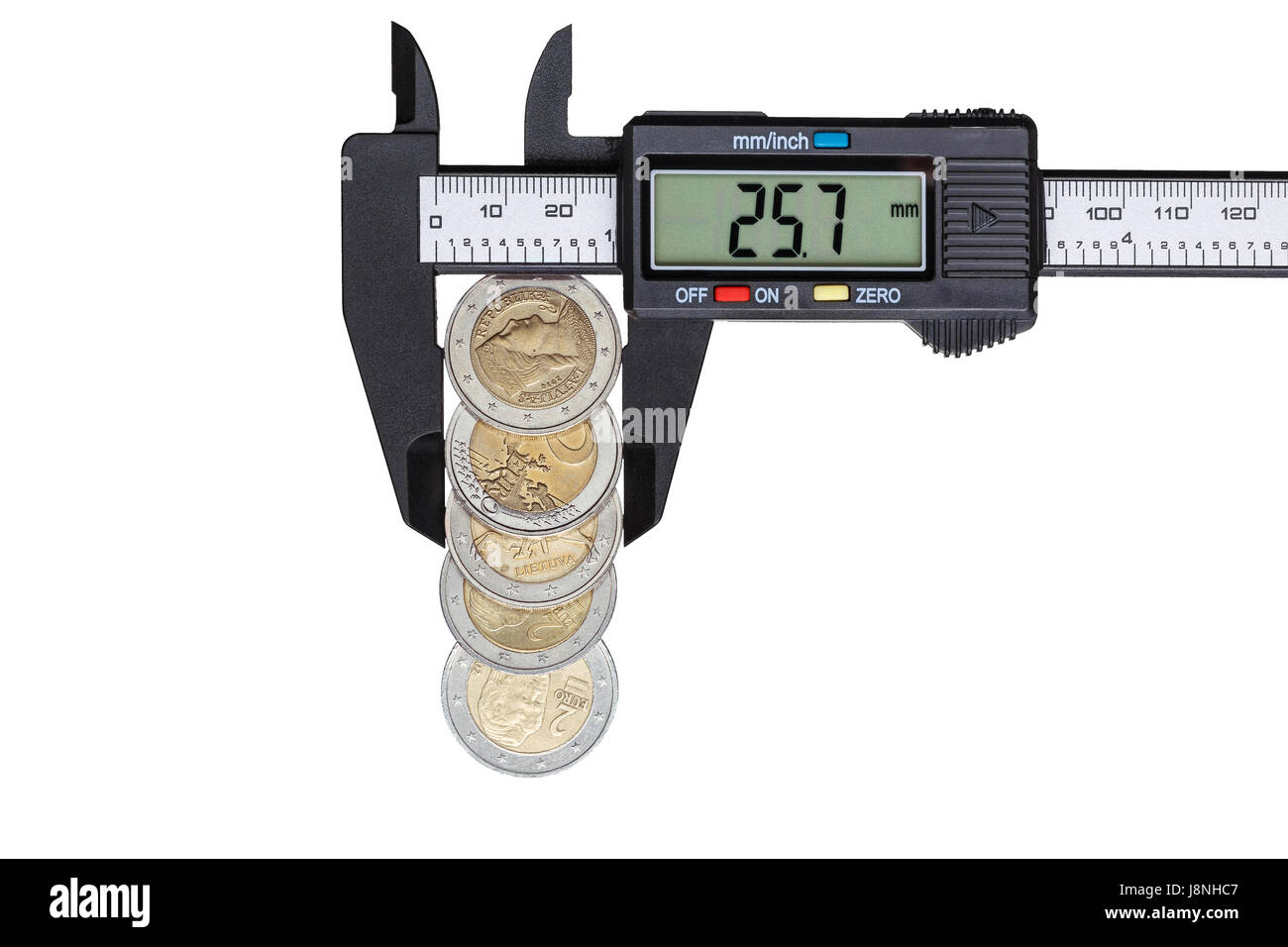 The digital caliper measures the diameter of 5 euro coins with a nominal value of 2 euros. Objects isolated on white - Stock Image