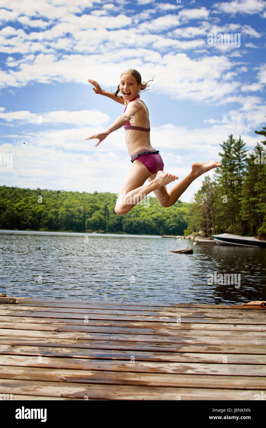 young teenage girl jumping off a dock at a lake in Ontario's cottage country Stock Photo