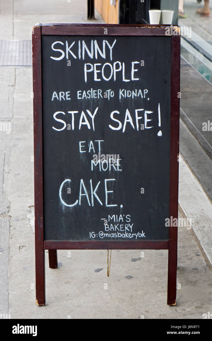 A very funny sign outside of Mia's bakery on Smith Street in Coblle Hill encouraging people to eat more cake. - Stock Image