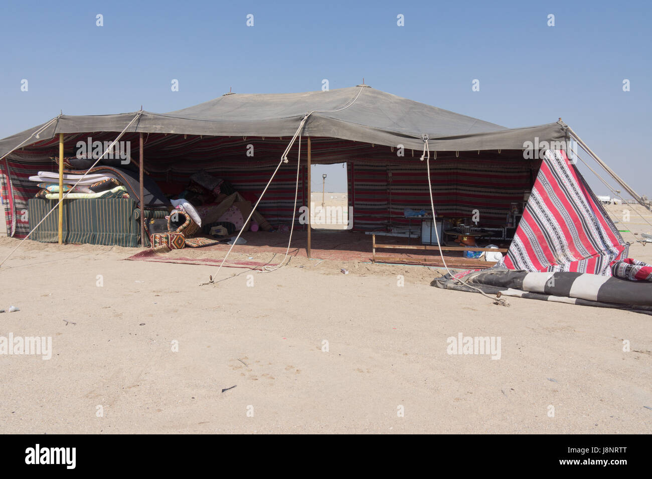 A discarded bedouin camp in Kuwait with camel hair tent. - Stock Image