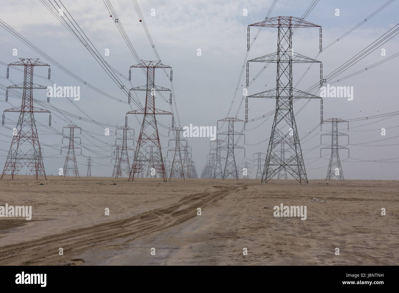 Large power lines through the desert providing the high demand for electricity in Kuwait City. - Stock Image