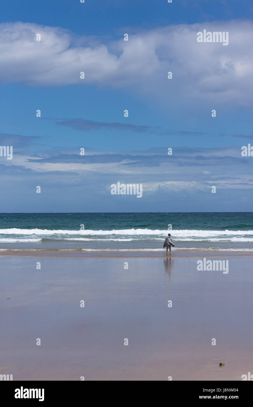 A lady stands looking out to the waves crashing onto the shore with a light breeze on an early spring day, with - Stock Image
