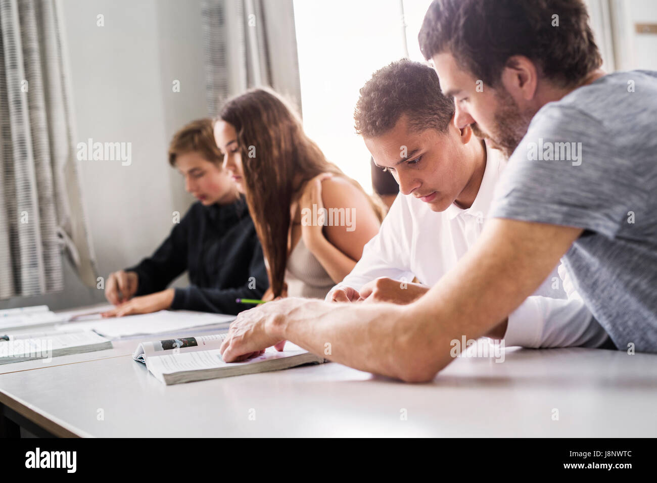 Teacher and students (14-15) in classroom Stock Photo