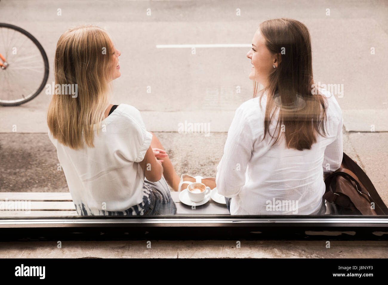 Young women talking outside of cafe Stock Photo