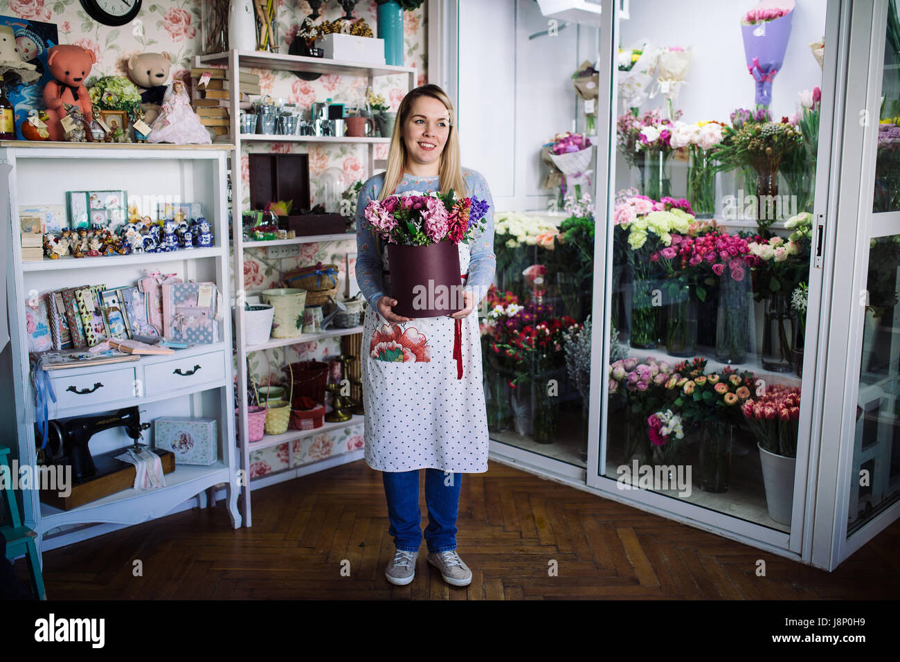 woman florist holding bouquet of hyacinth indoor in flower shop - Stock Image