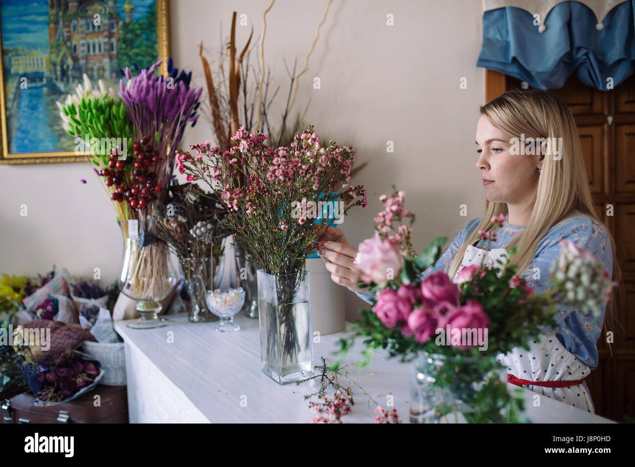 woman florist making bouquet of pink flowers indoor. Female florist preparing bouquet  in flower shop - Stock Image