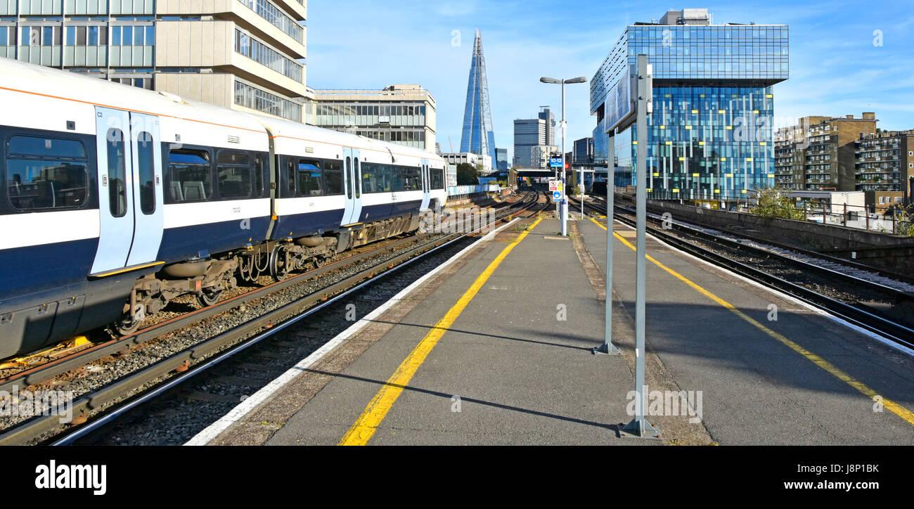 Waterloo East train station platform with public transport electric passenger train and the Shard skyscraper landmark - Stock Image