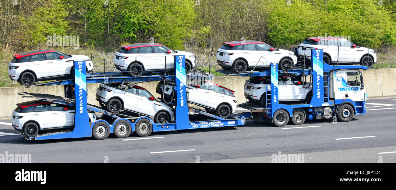 Supply chain logistics using loaded HGV car transporter lorry truck to move eight new red & white Range Rover - Stock Image
