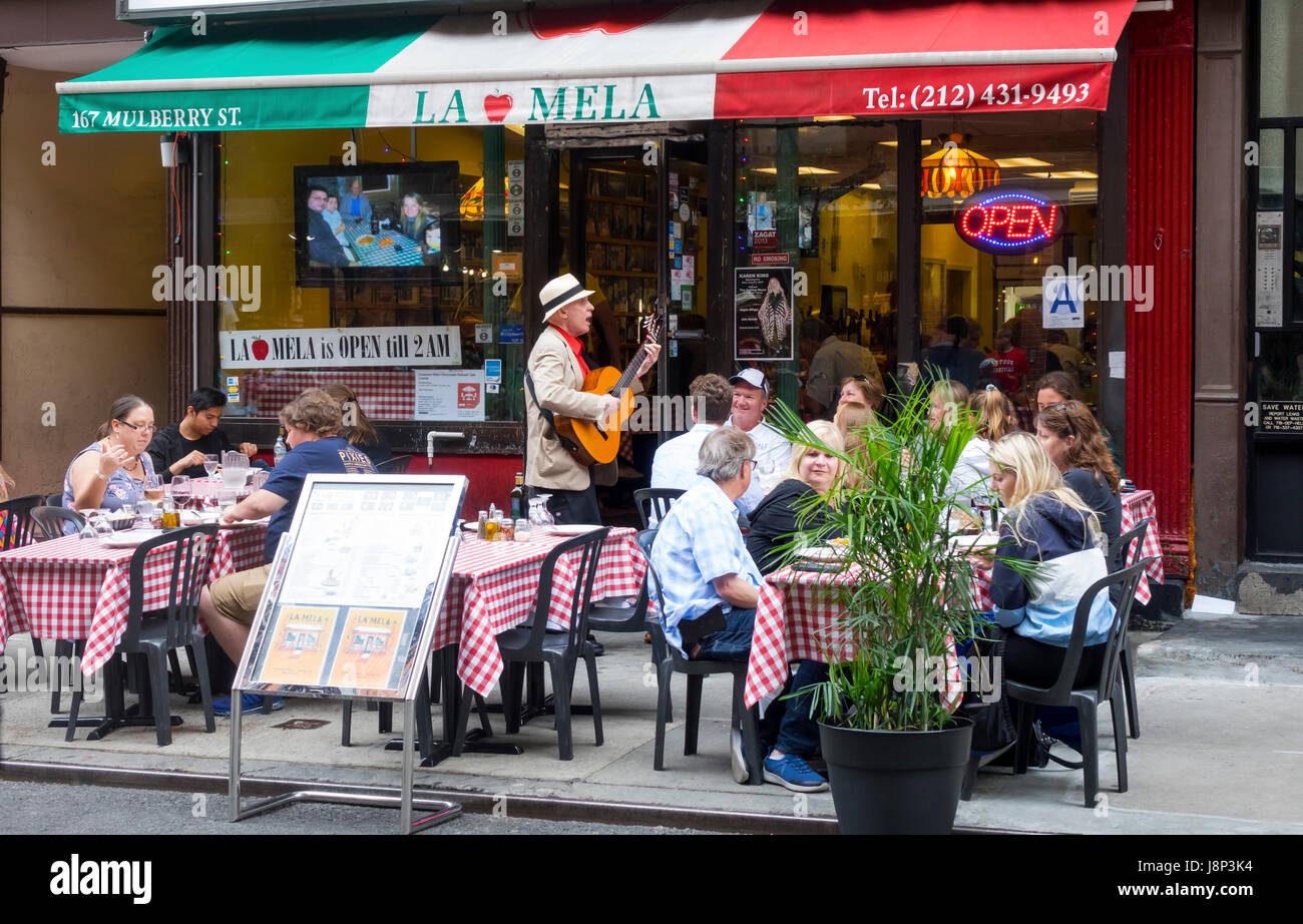 An Italian senior sings and plays for the alfresco dinners at La Mela, a restaurant on Mulberry Street in Little - Stock Image