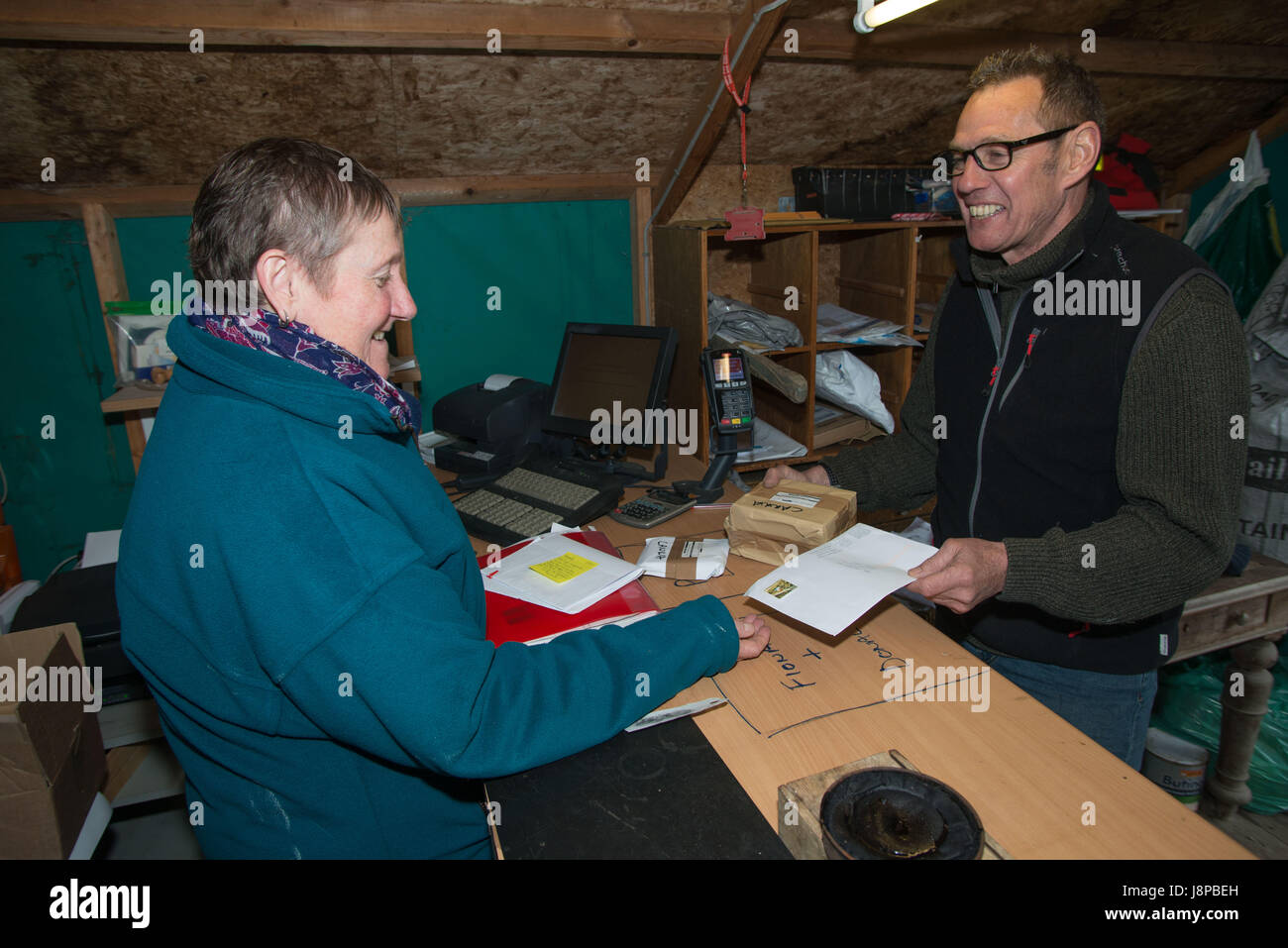 Winefride MacKinnon serving Patrice Charymettan from Reims, France  in the post office on the Island of Canna, inner - Stock Image