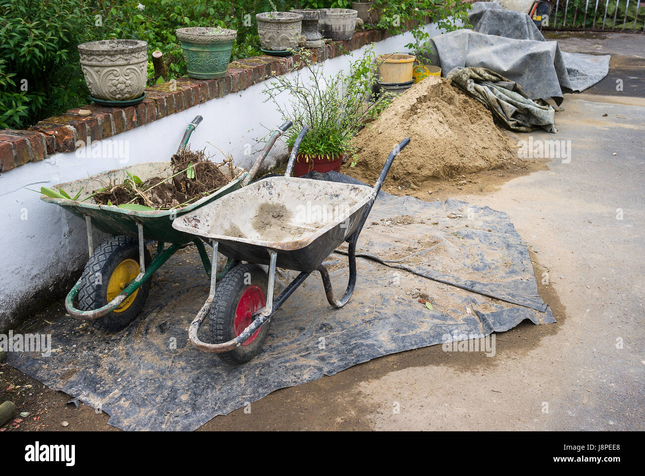 Two builders wheelbarrows stored neatly at the end of the day on site - Stock Image