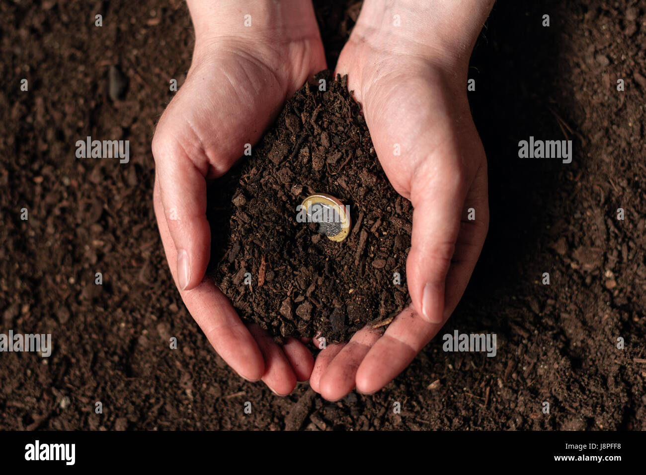 Making income from agricultural activity and earning extra money, female farmer handful of soil with euro coin - Stock Image
