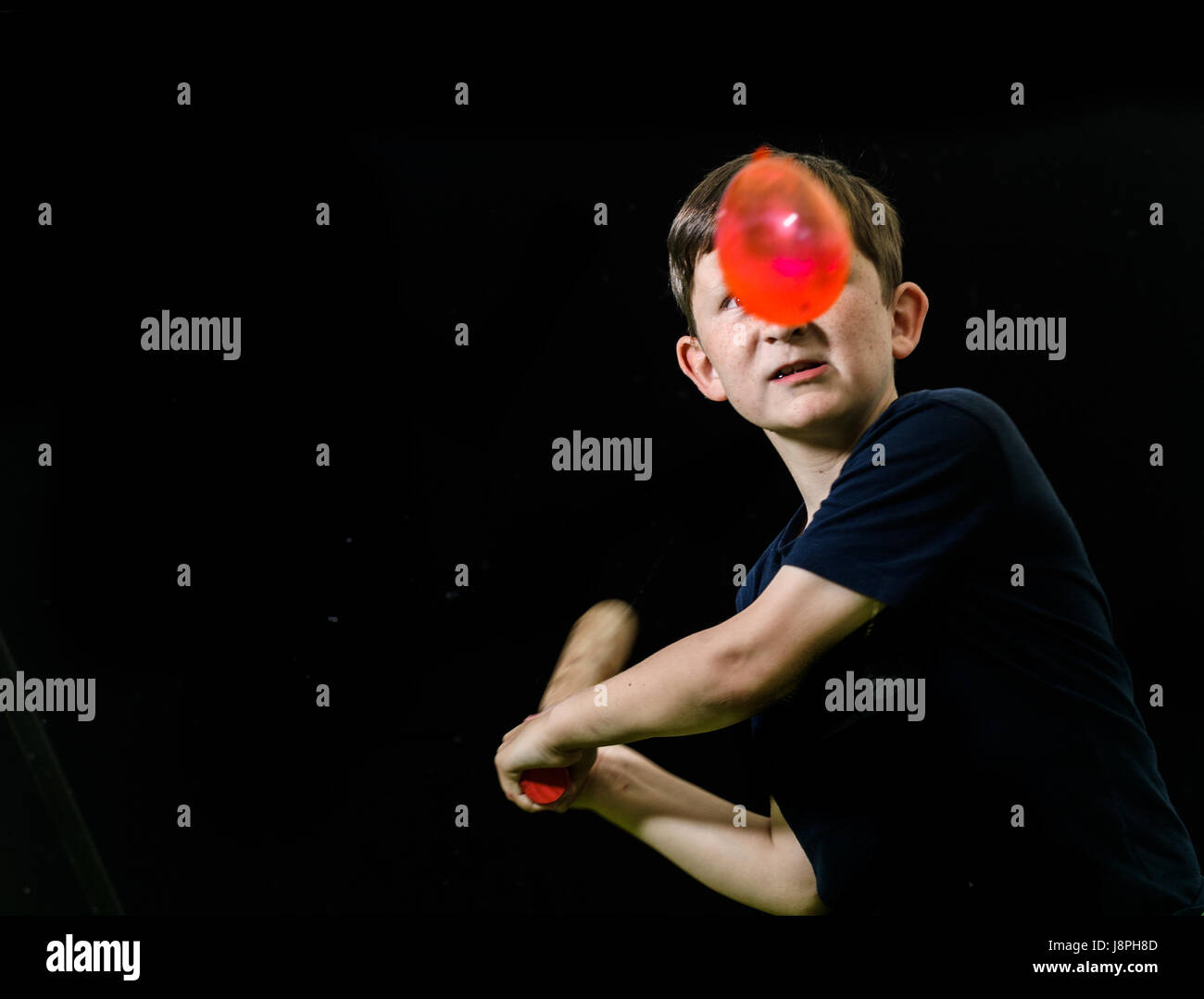 Young boy, with a look of determination and concentration on his face, takes aim with his bat at a red water balloon - Stock Image