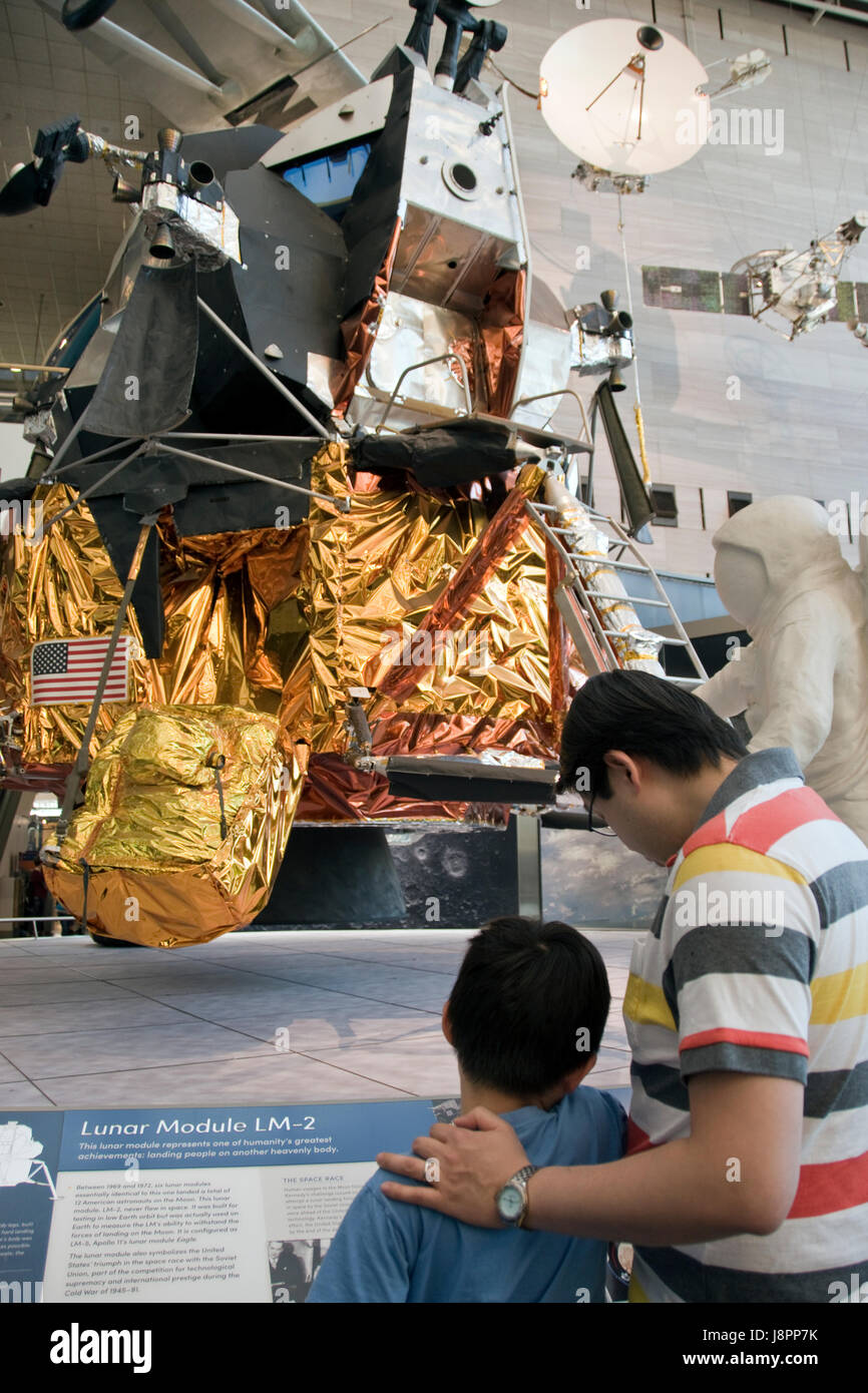 Father and son look at a lunar module, which landed men on the moon in the Apollo program, at the Nat. Air & - Stock Image