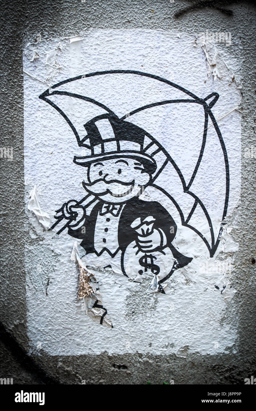 Mr. Monopoly the capitalist in Hong Kong. Along with a bag of cash, he also holds an umbrella, symbolic of the Umbrella - Stock Image