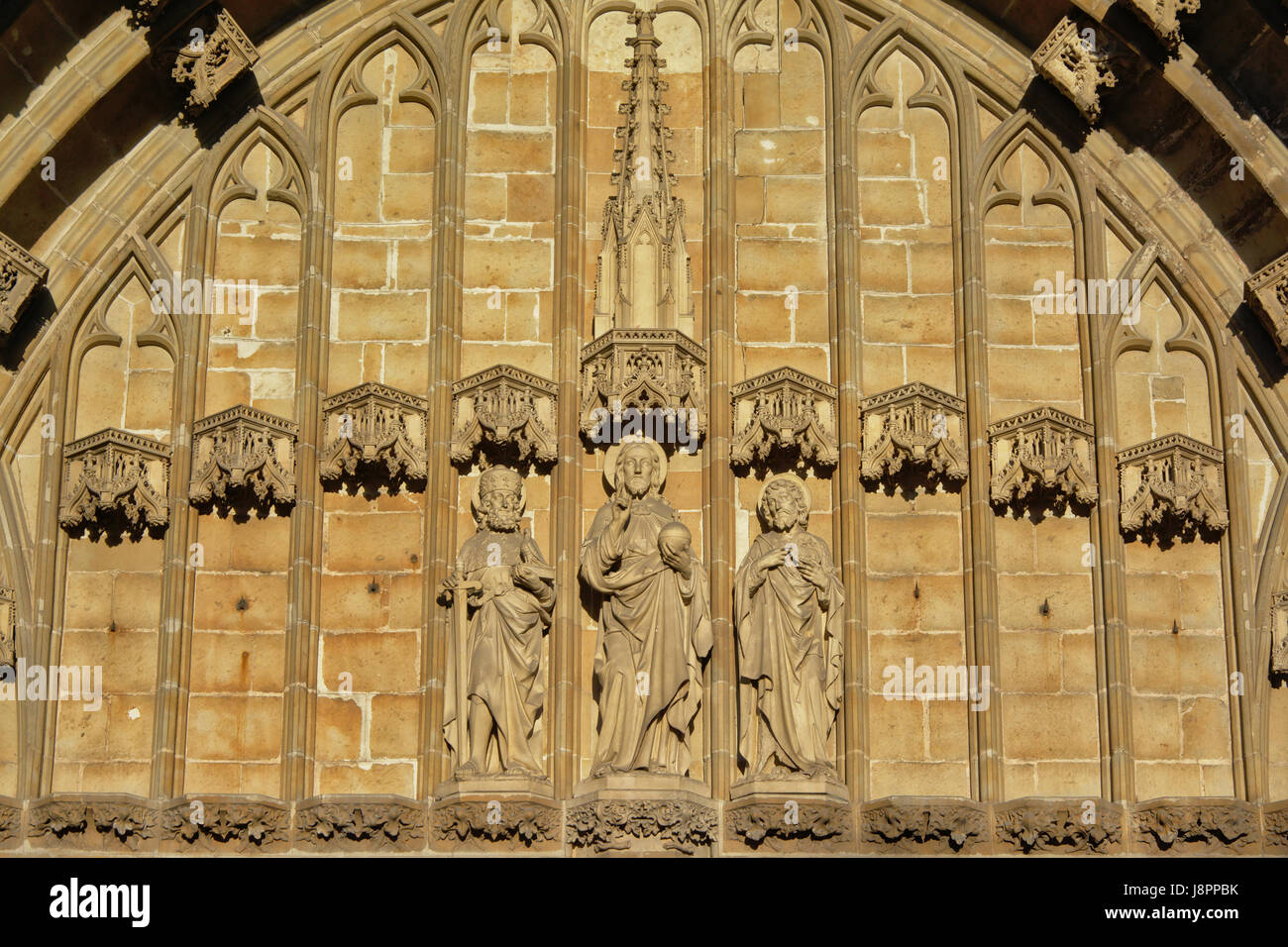 Statues of three saints above the entrance of Saint Bavo Cathedral, Ghent, Belgium - Stock Image