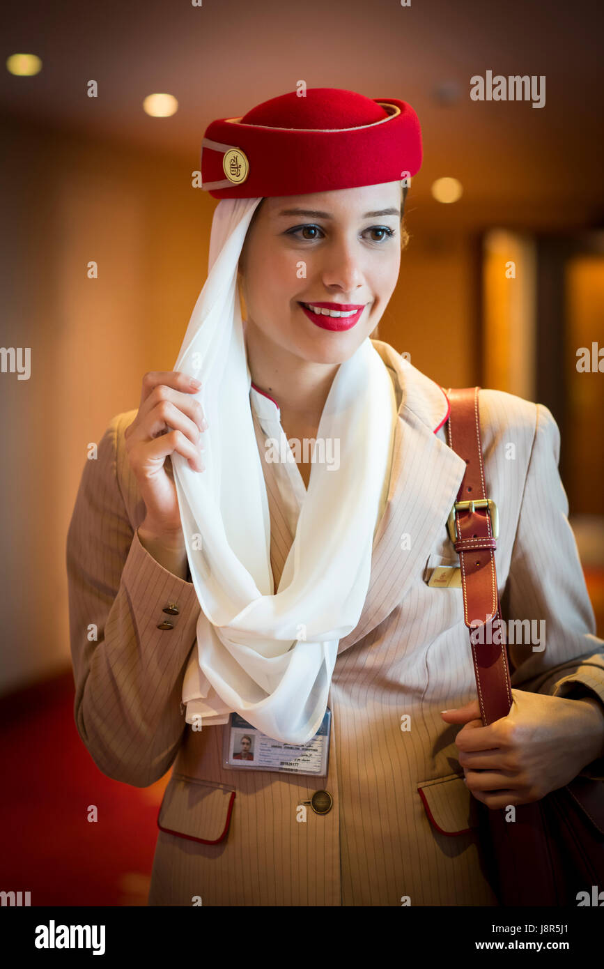 Young attractive Emirates cabin crew and flight attendant at London Heathrow Airport awaiting Emirates Airline A380 - Stock Image