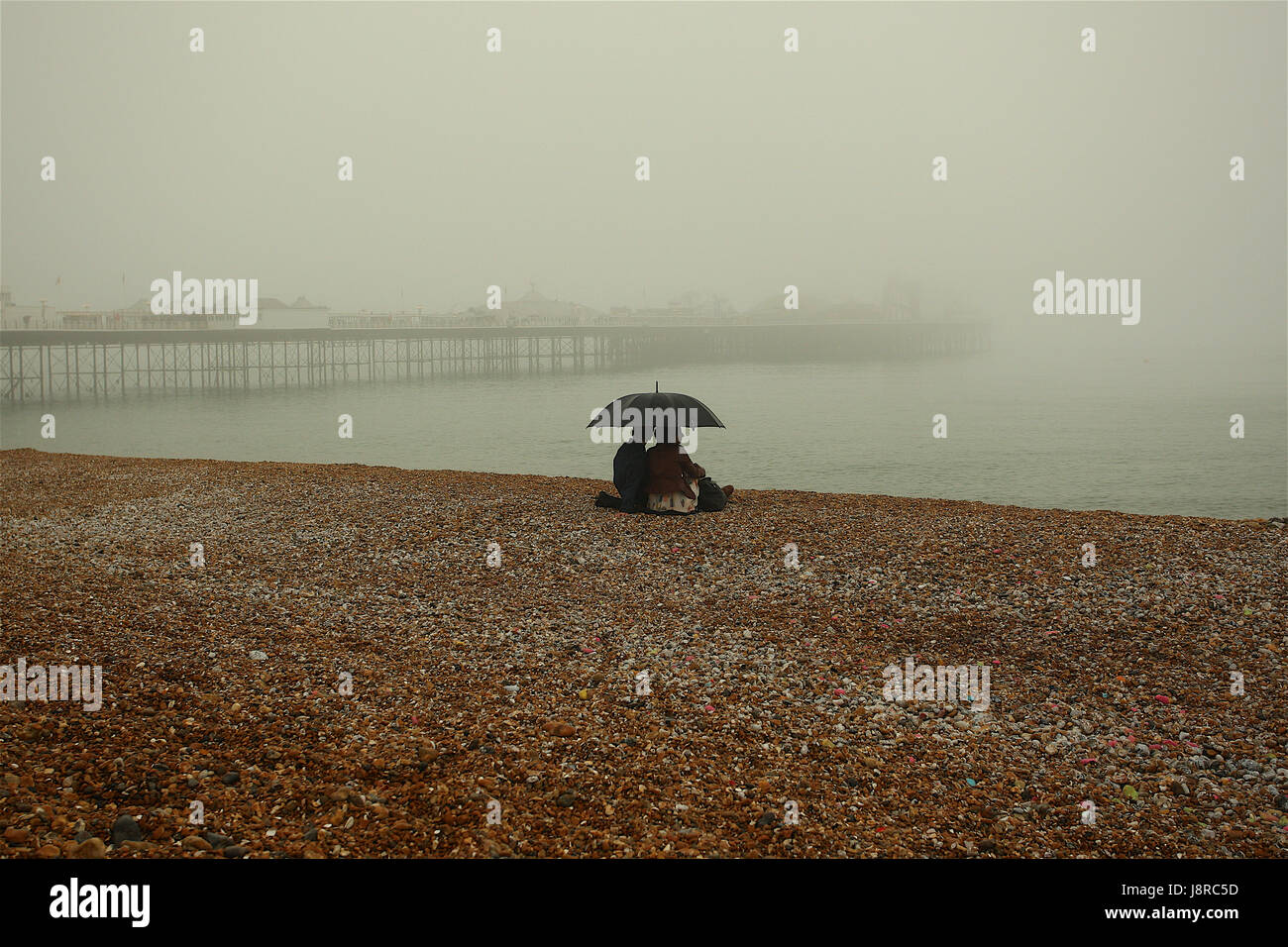 A foggy day in Brighton doesn't stop visitors enjoying their time on the beach in Brighton East Sussex UK - Stock Image