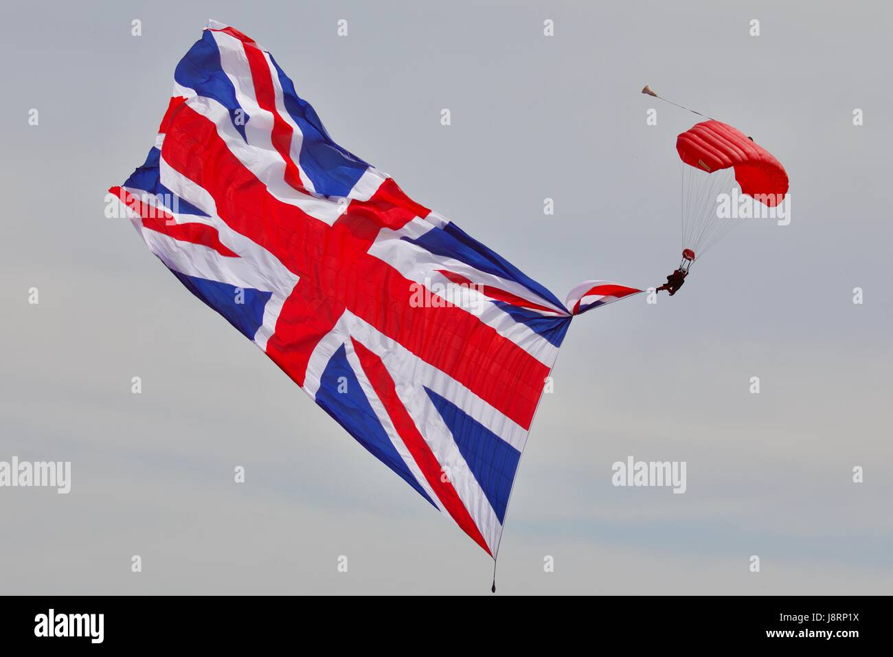 The Red Devils parachute display team with a giant union jack flag - Stock Image