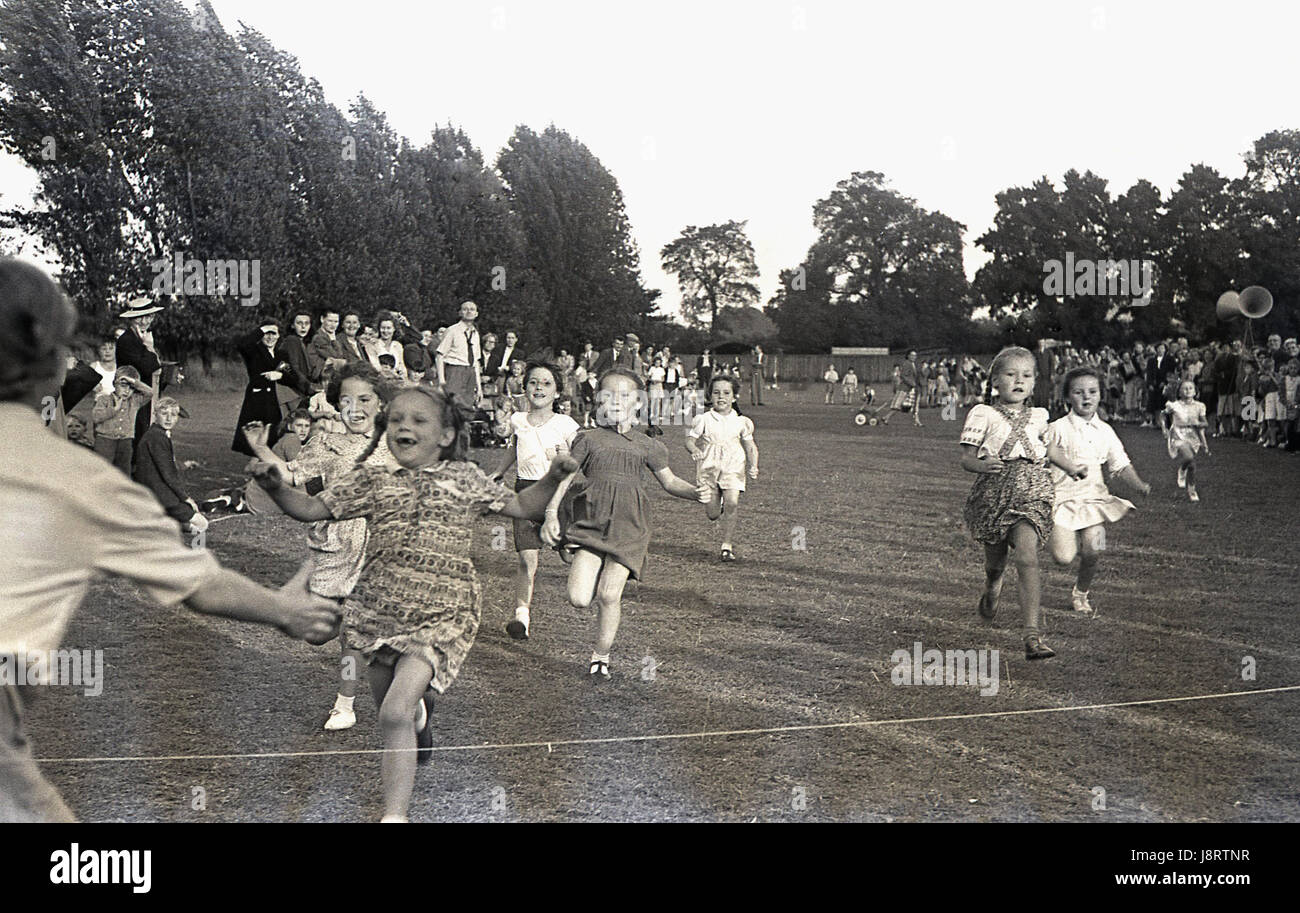 1950s. historical, young girls running in the 60 yard dash at a school sports day, with one joyful youngster about - Stock Image