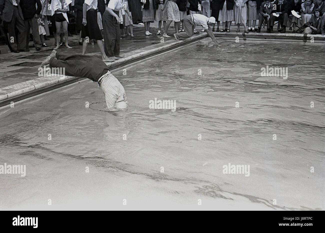 1950s, outdoor swimming gala, adult males taking part in a race, dive into the pool fully clothed wearing swimcaps, - Stock Image
