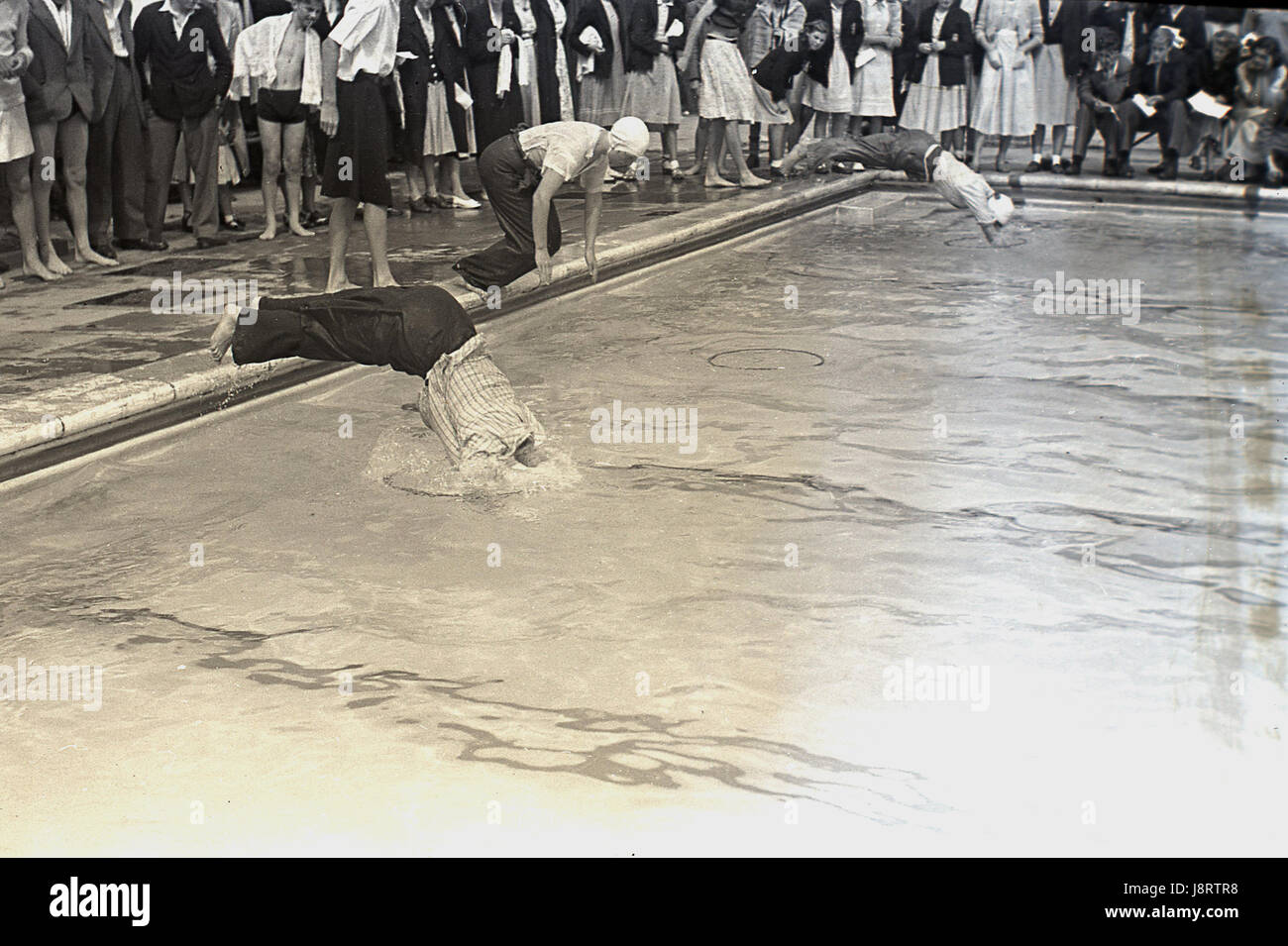 1950s, outdoor swimming gala, adult males dive into the pool fully clothed with swimcaps, England, UK. - Stock Image
