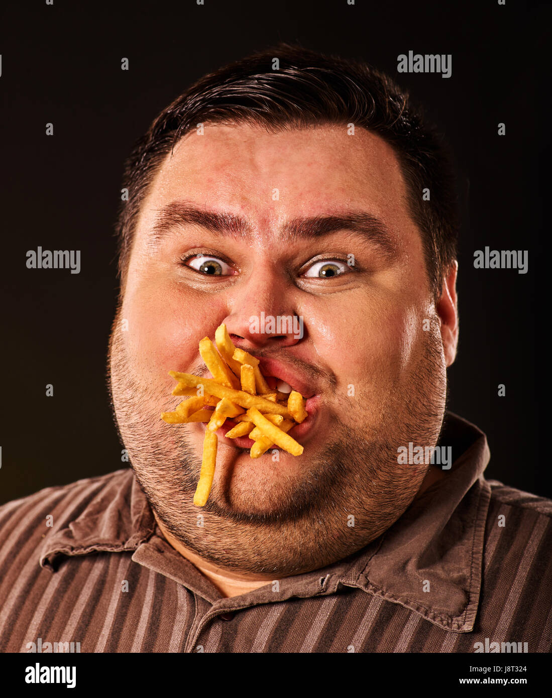 fat man eating fast food french fries for overweight person stock