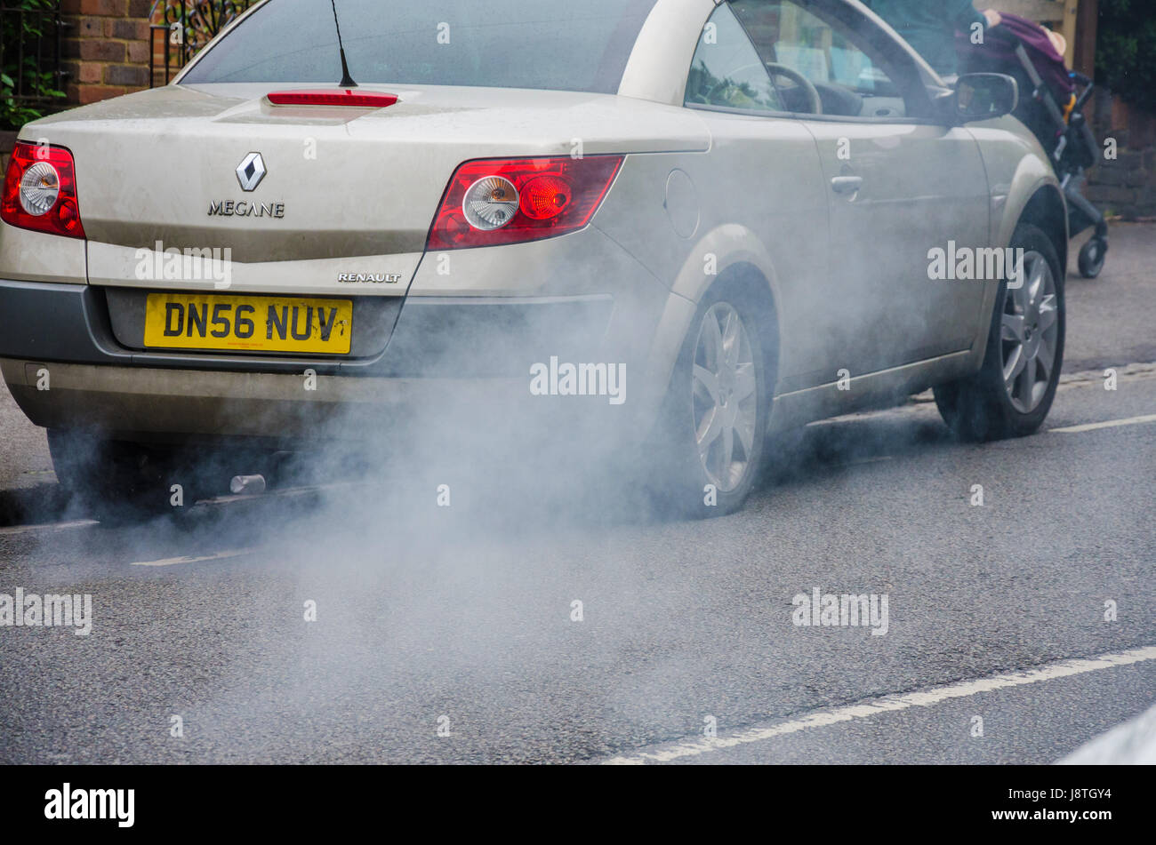 A car producing smoke form it's exhaust, - Stock Image