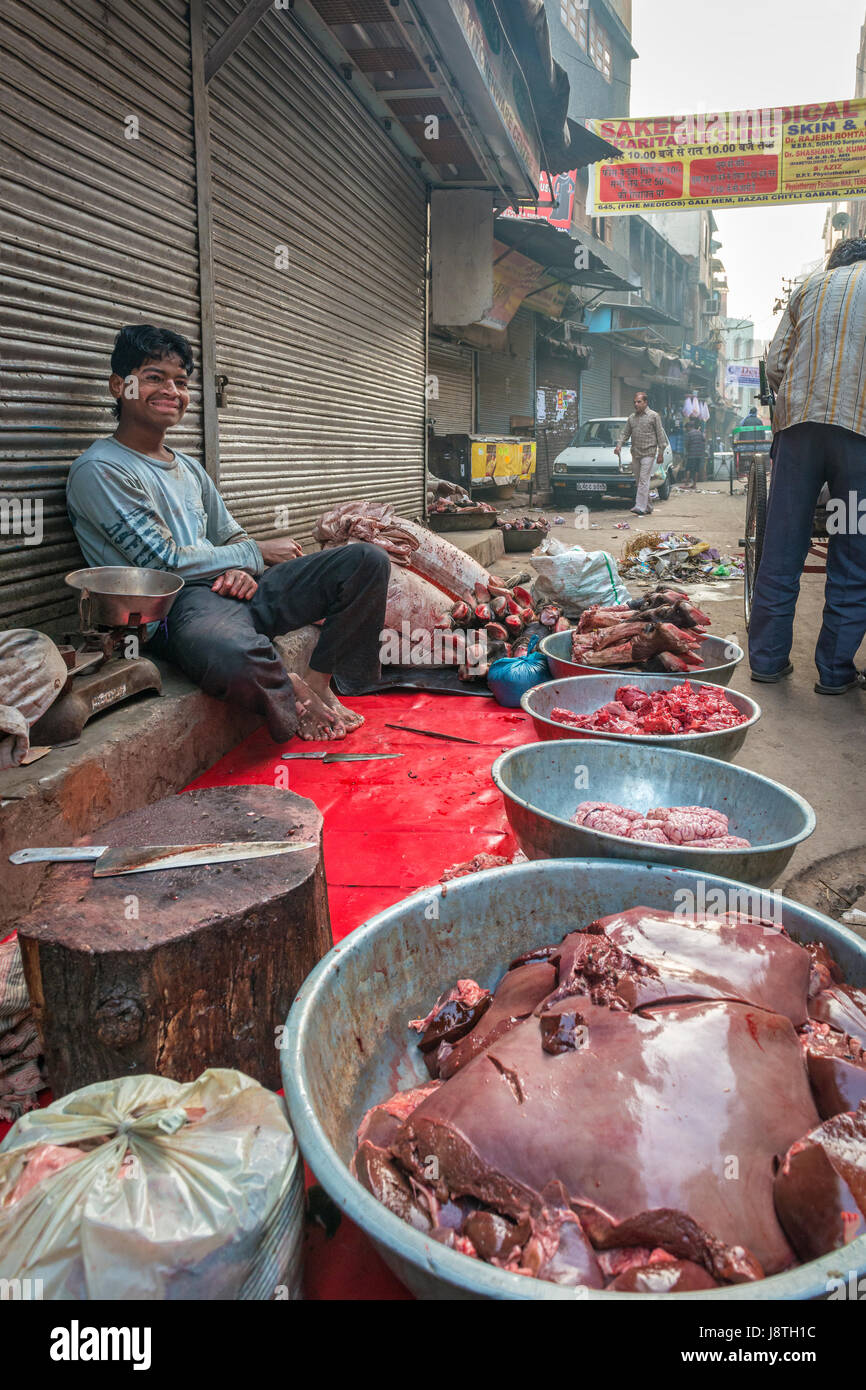 Delhi, India - 10 November 2012 - Young man selling fresh meat on the sidewalk, a customary way of street trade - Stock Image