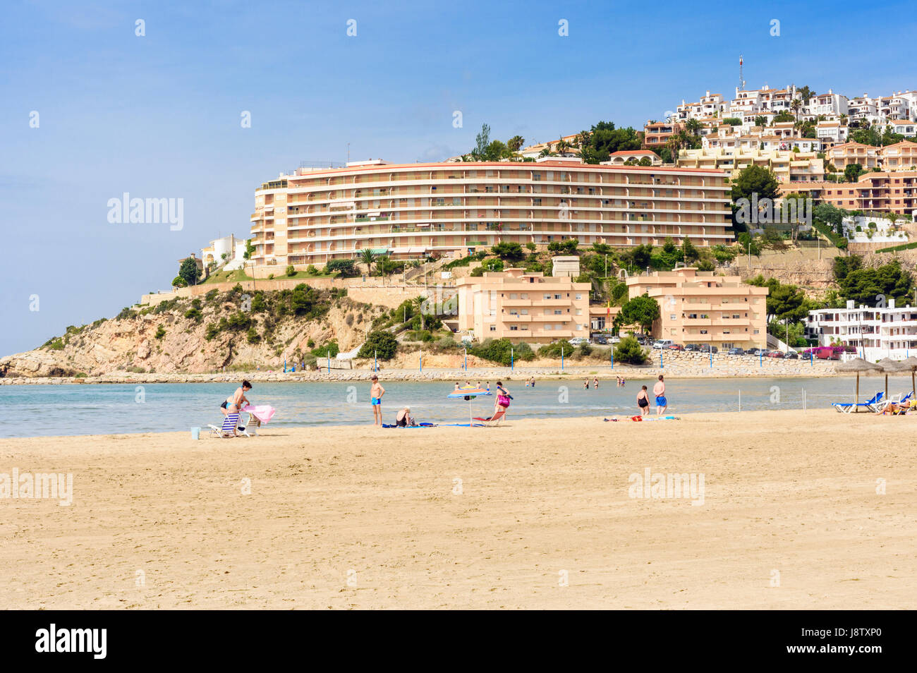People on Playa Sur, the South Beach overlooked by modern coastal development along the Costa del Azahar, Peniscola, - Stock Image