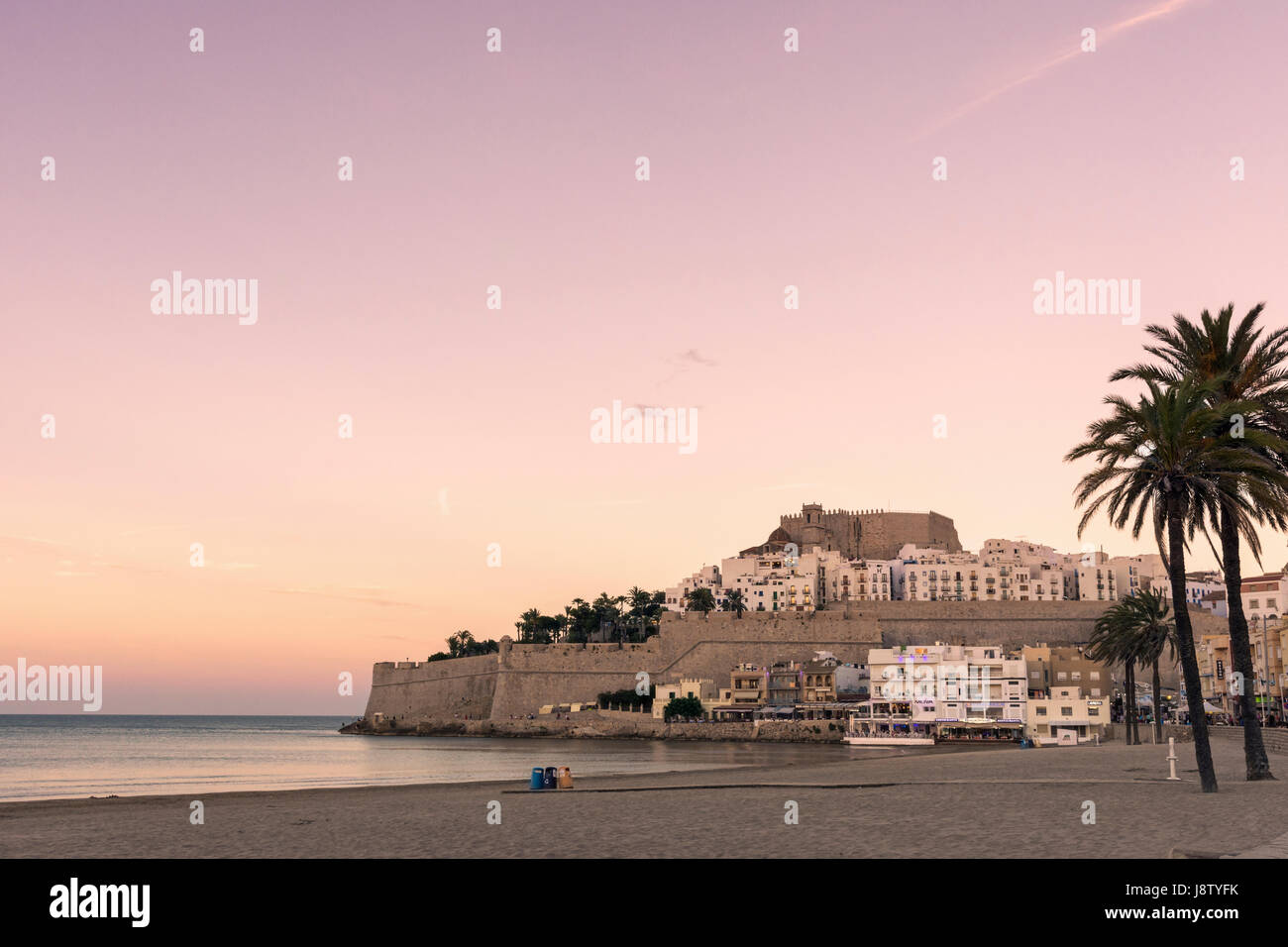 Sunset over Papa Luna's Castle and old town overlooking the beach, Playa Norte, Peniscola, Castellon, Spain - Stock Image