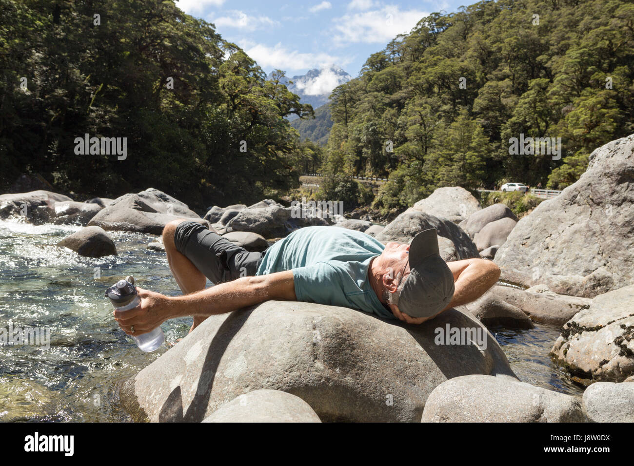 senior man resting on a rock by a river in Fiordland New Zealand - Stock Image