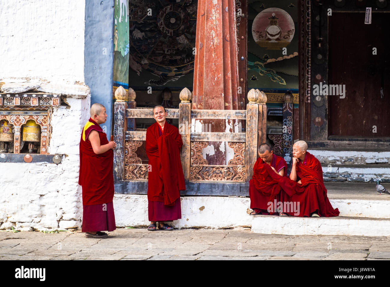 Buddhist monks congregating outside the monastery after a chanting session at Trongsa Dzong, Bhutan. - Stock Image