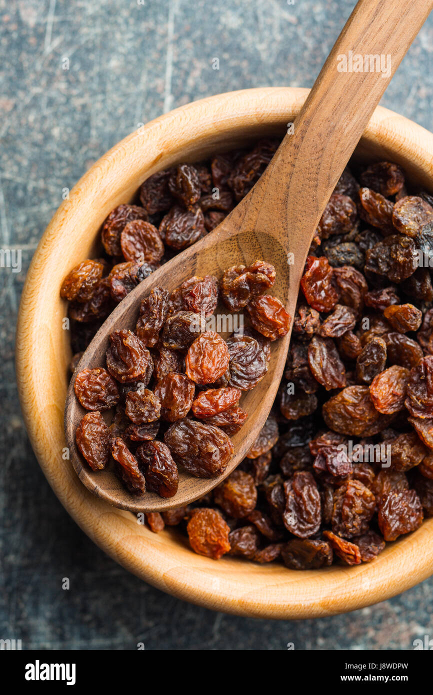 Sweet dried raisins in wooden spoon on old kitchen table. Top view. - Stock Image