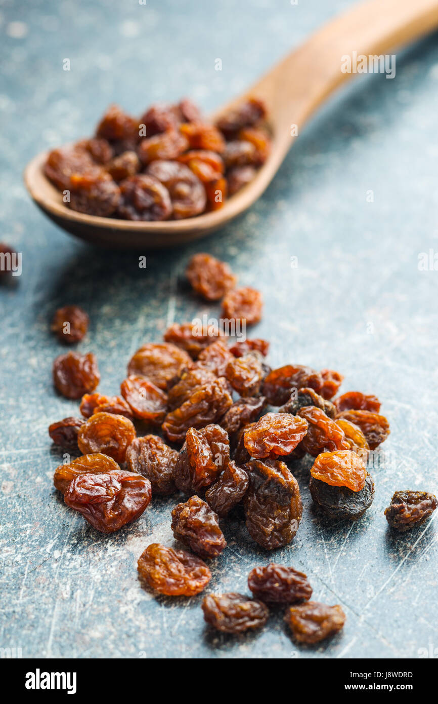 Sweet dried raisins on old kitchen table. - Stock Image