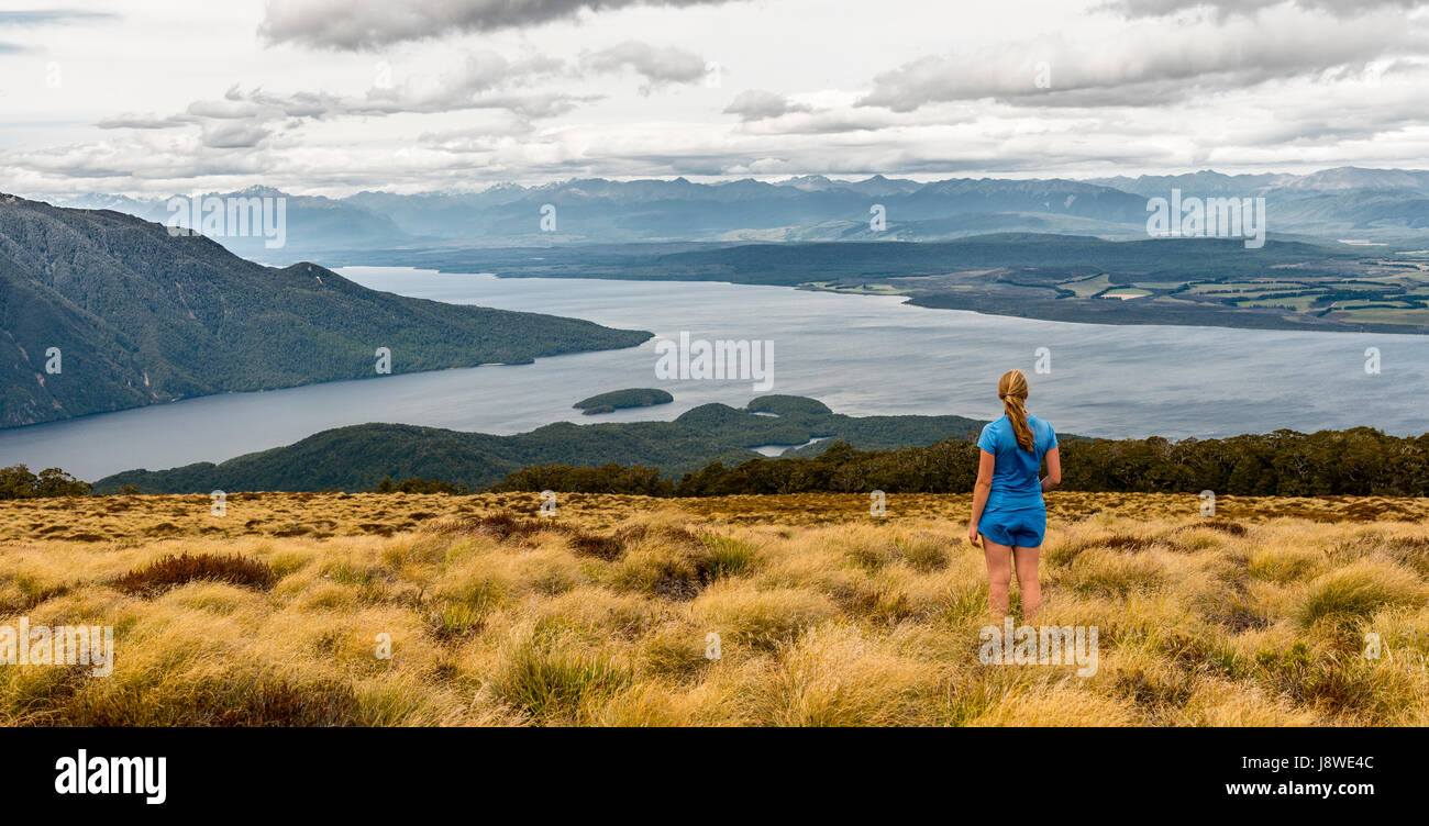 Female hiker looking at lake Te Anau and Southfiord, Kepler Track, Fiordland National Park, Southland, South Island, - Stock Image