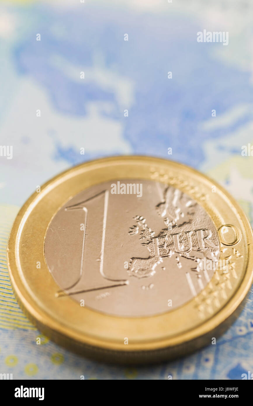 One Euro coin on top of twenty Euro paper currency bank note - Stock Image