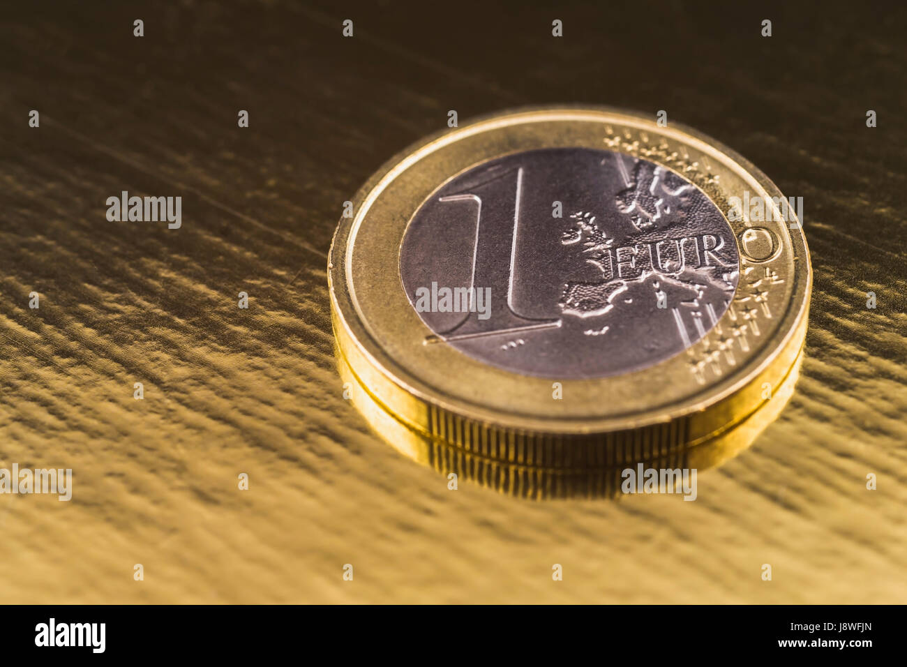 One Euro coin on gold background - Stock Image