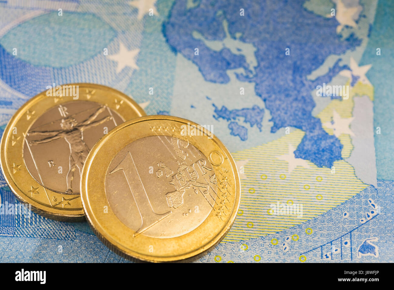 One Euro coins on top of twenty Euros paper currency bank note - Stock Image