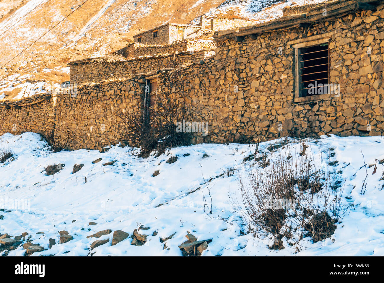 Mud brick houses with snow covered ground in the Himalayan mountains of Nepal. - Stock Image