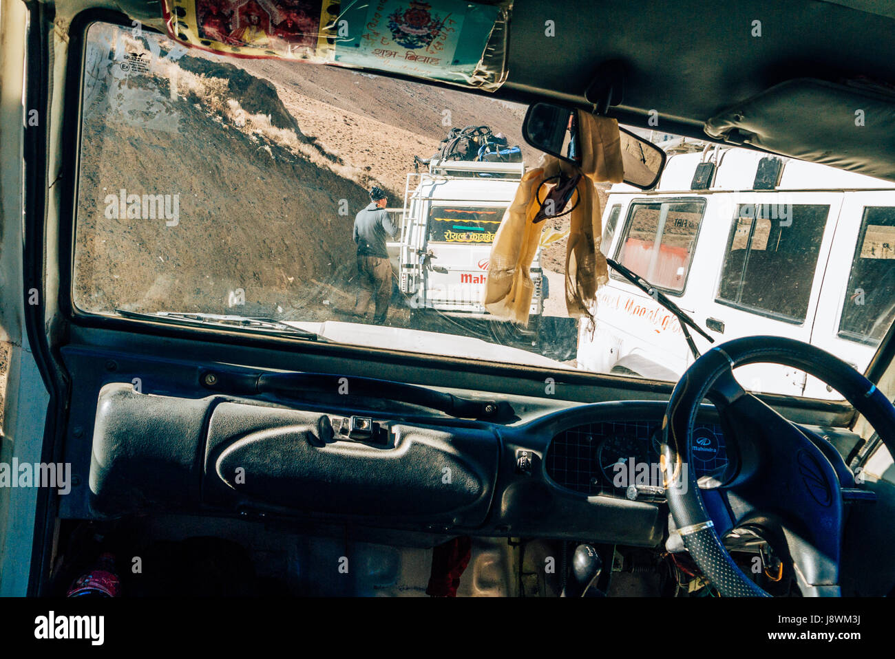 Convoy of jeeps along the rugged Himalayan mountains dirt road in Nepal. - Stock Image