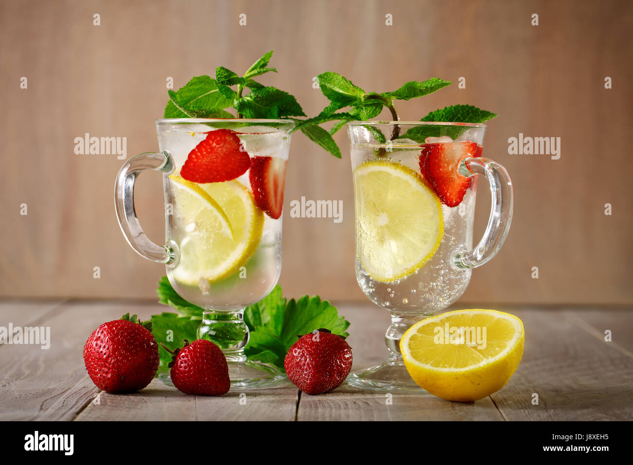 Fresh summer healthy drink with lemon and strawberries with ice. - Stock Image