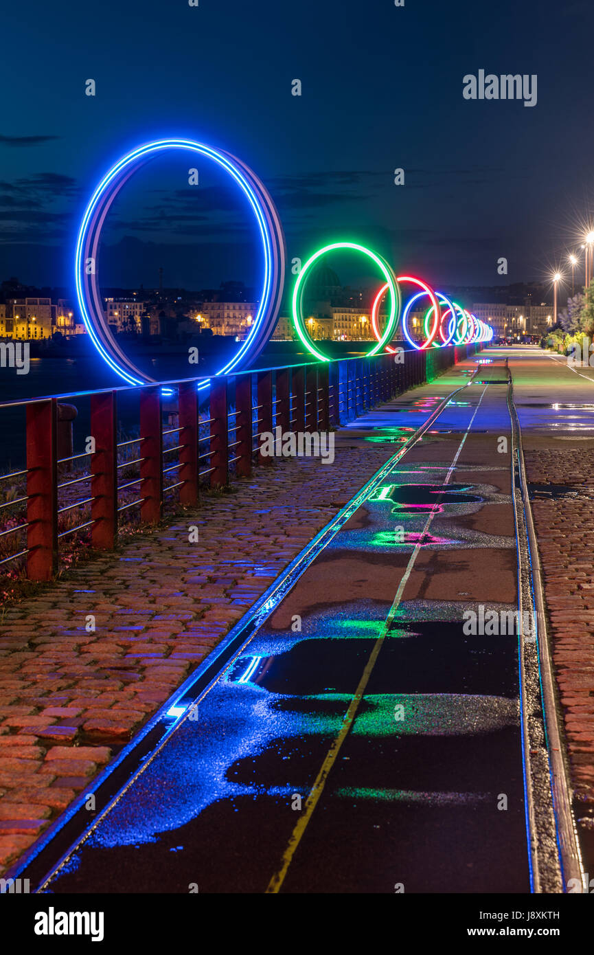 The luminous rings on the Nantes island by night with the light reflection on the puddles - Stock Image
