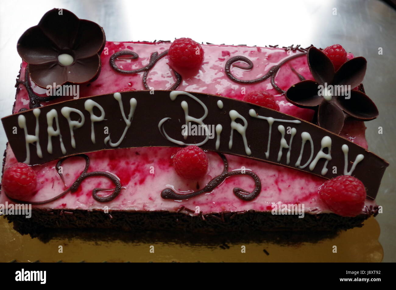 Chocolate Birthday Cake With Flower And Raspberry Decorations A HAPPY BIRTHDAY Sign