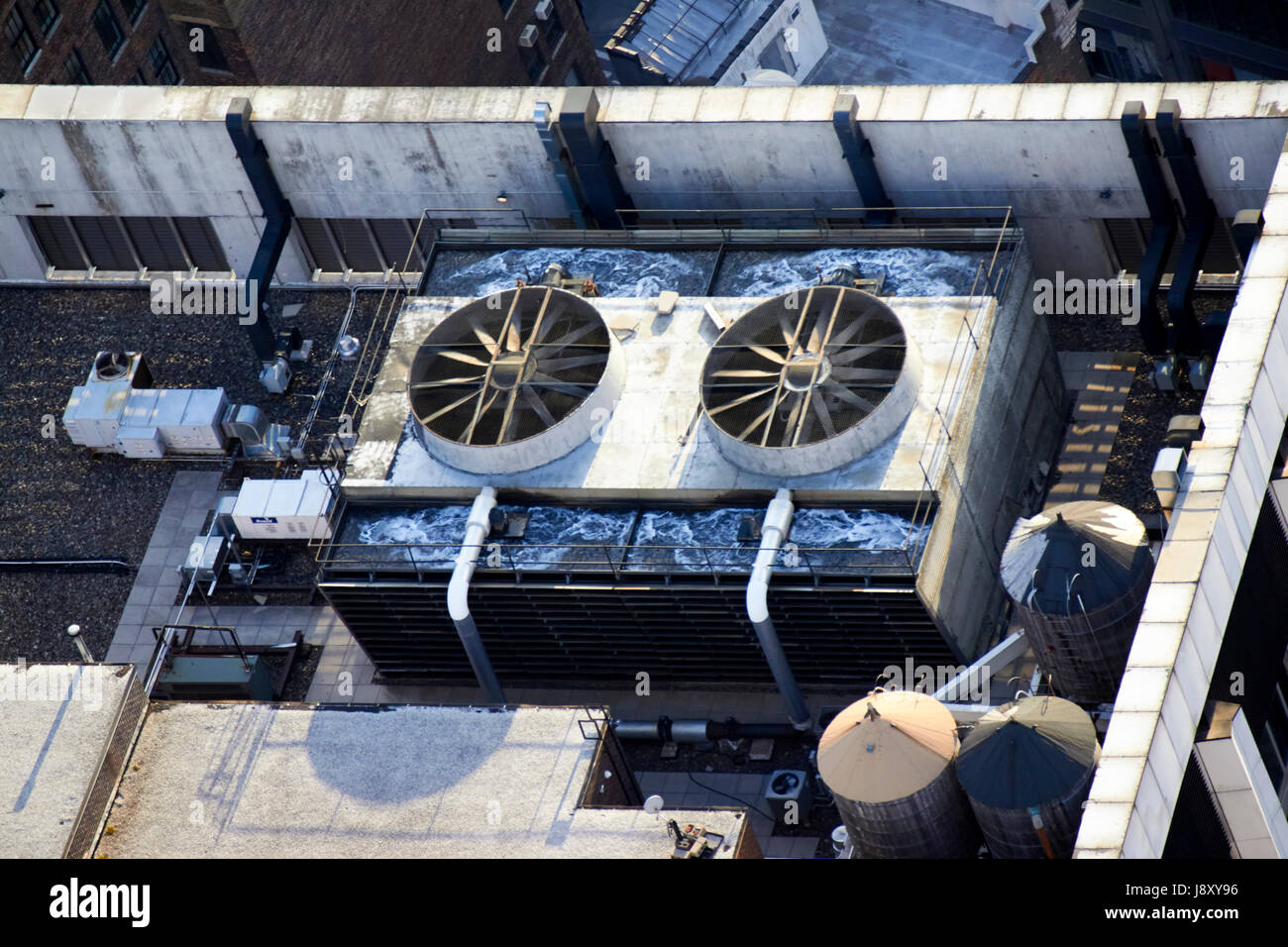 industrial large air conditioning system and wooden water towers on top of buildings in midtown manhattan New York - Stock Image